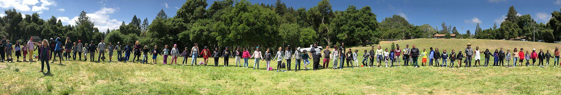 Many kids holding hands in line in field